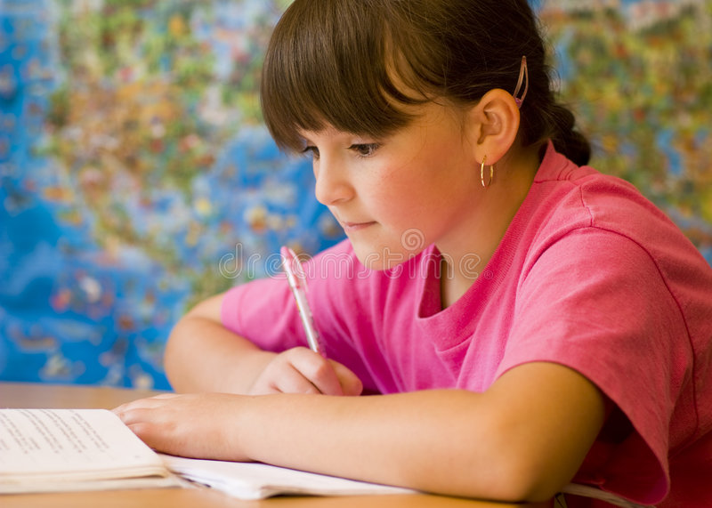 Girl doing homework. Concentrated young girl doing her school home-work royalty free stock image