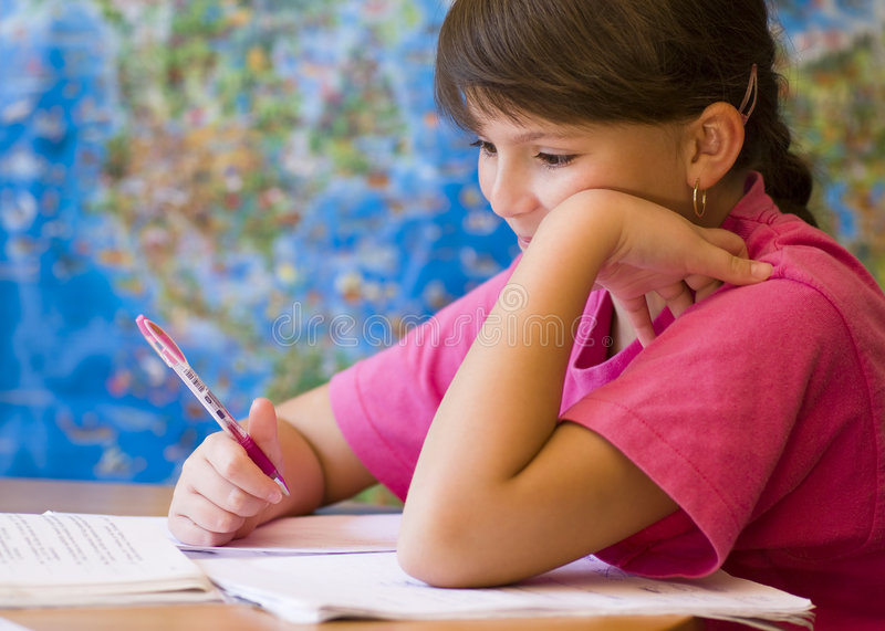 Girl doing homework. Young girl doing his homework royalty free stock photos