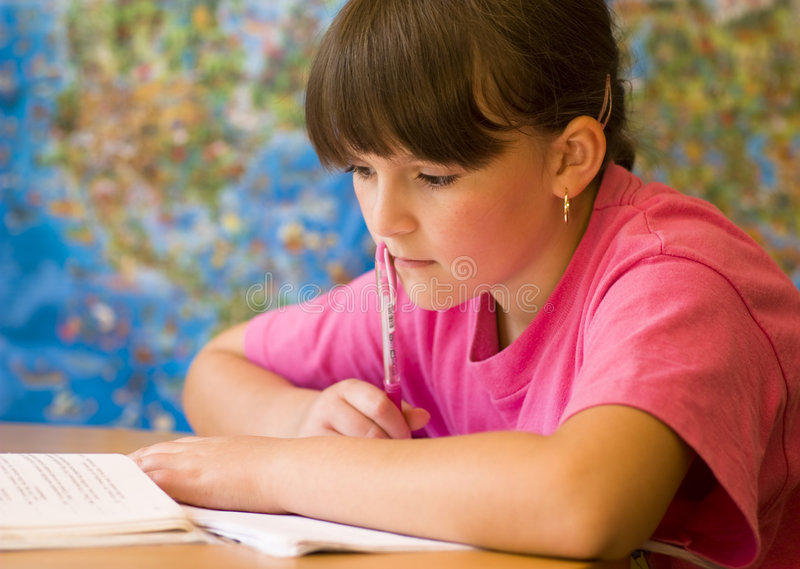 Girl doing homework. Concentrated young girl doing her school home-work royalty free stock images