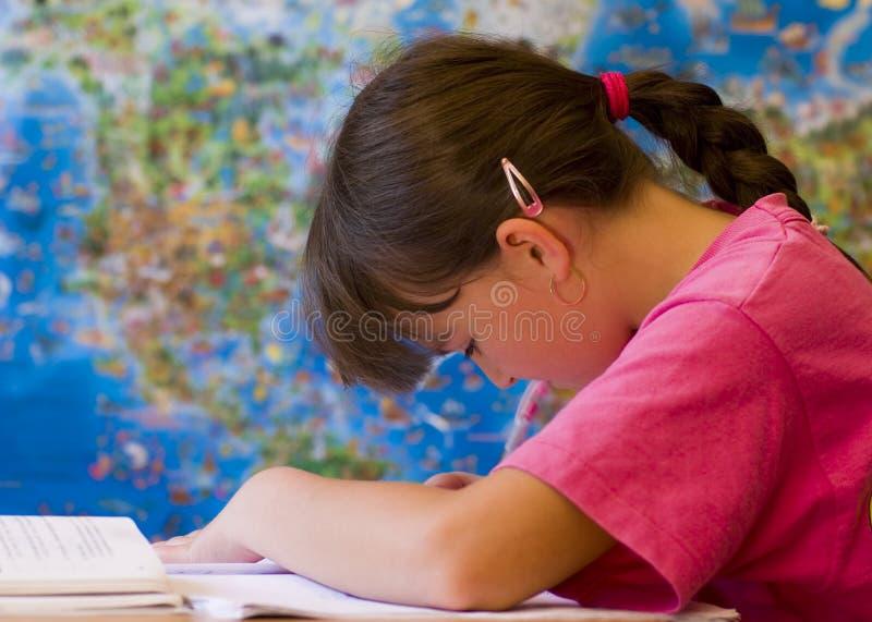Girl doing homework. Young girl doing her school home-work stock photography