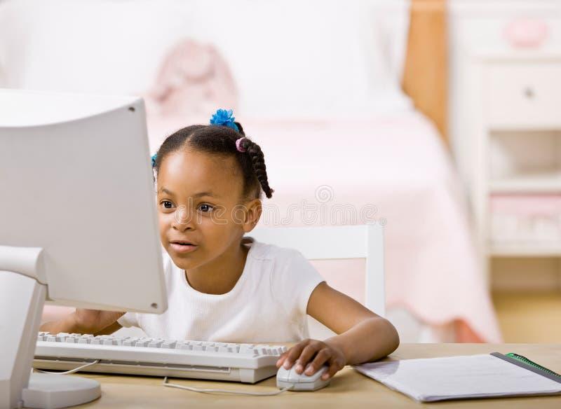 Girl doing homework on computer in bedroom