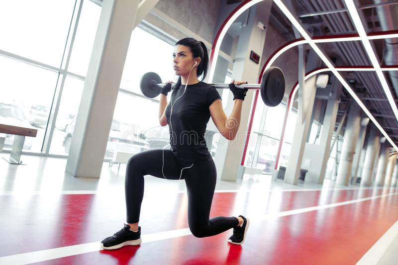 Girl doing lunges with barbell in modern gym stock photography