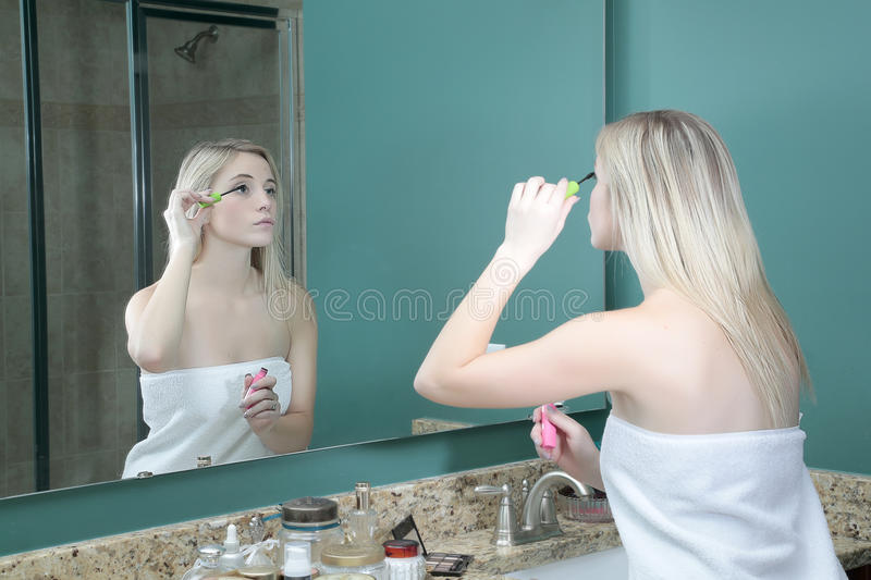 Girl doing makeup in front of mirror stock images