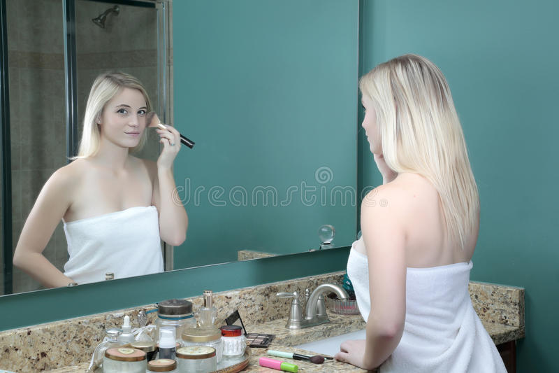 Girl doing makeup in front of mirror royalty free stock photo