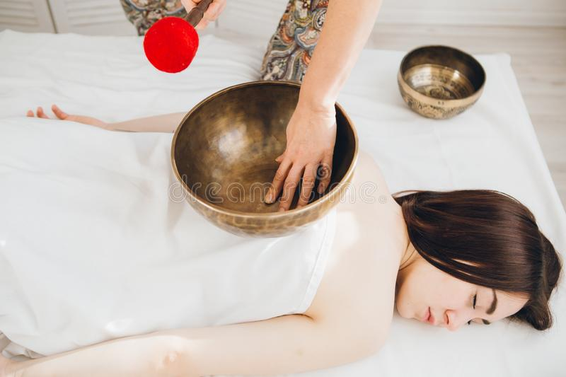 Girl doing massage therapy singing bowls in the Spa royalty free stock photo