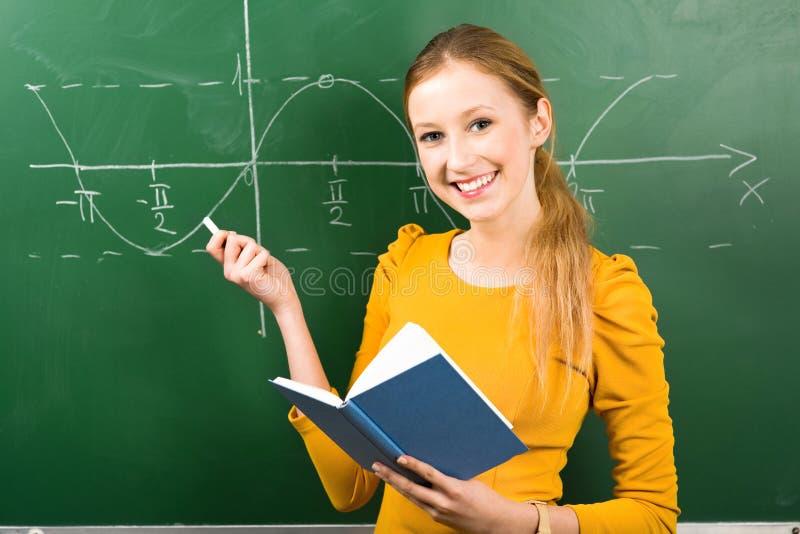 Girl Doing Math on Chalkboard royalty free stock image