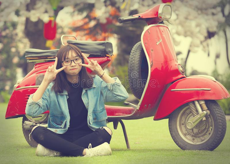 Girl Doing Peace Sign Indian Sitting in Front of Red Scooter Motorcycle royalty free stock photo