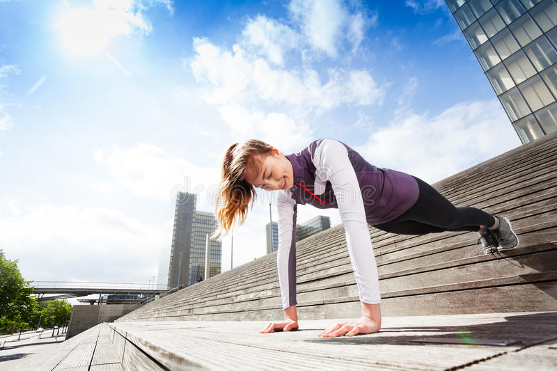 Girl doing plank exercises outdoors on city stairs royalty free stock photos