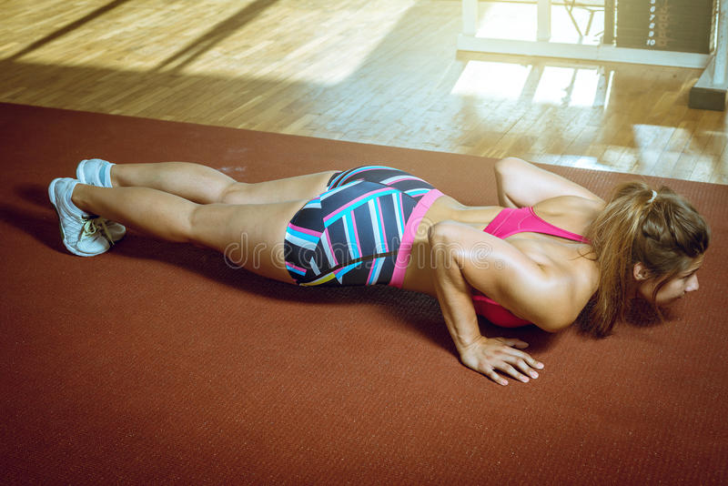 Girl doing push-ups in gym. Young adult girl doing push ups exercise in gym stock images