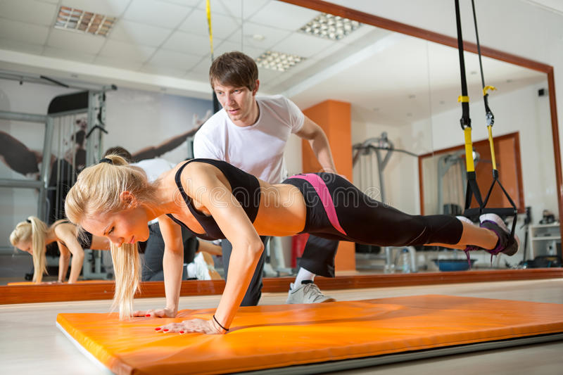 Girl doing pushups with resistance band. In the presence of a personal trainer stock photo