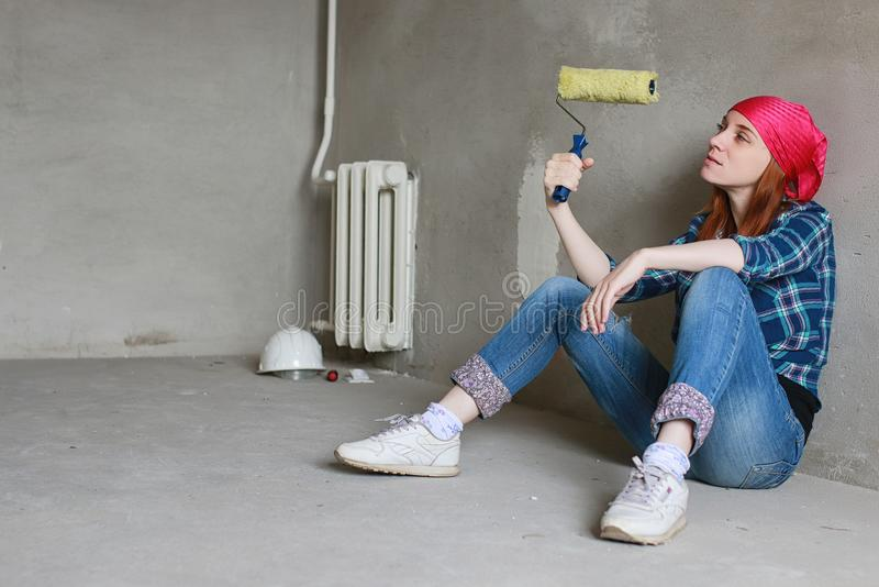 The girl is doing repairs in the apartment. Home moving to a new apartment. The worker makes repairs, plastered and royalty free stock image