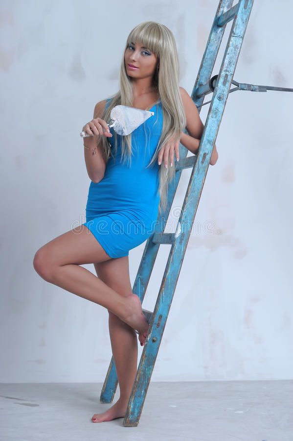 Girl doing repairs at home. Beautiful slim blonde in a blue dress royalty free stock photography