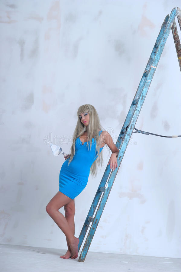 Girl doing repairs at home. Beautiful slim blonde in a blue dress royalty free stock photo