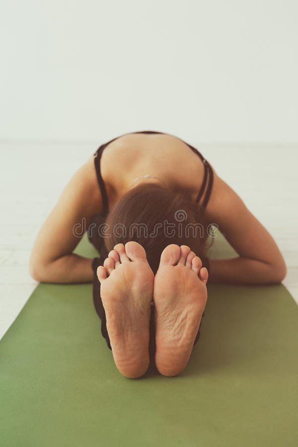 Girl doing seated forward bend. Seated forward bend. Intense dorsal stretch girl is doing yoga while holding a difficult asana stock images