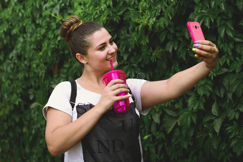 Girl doing selfie on a background of green plants royalty free stock photography