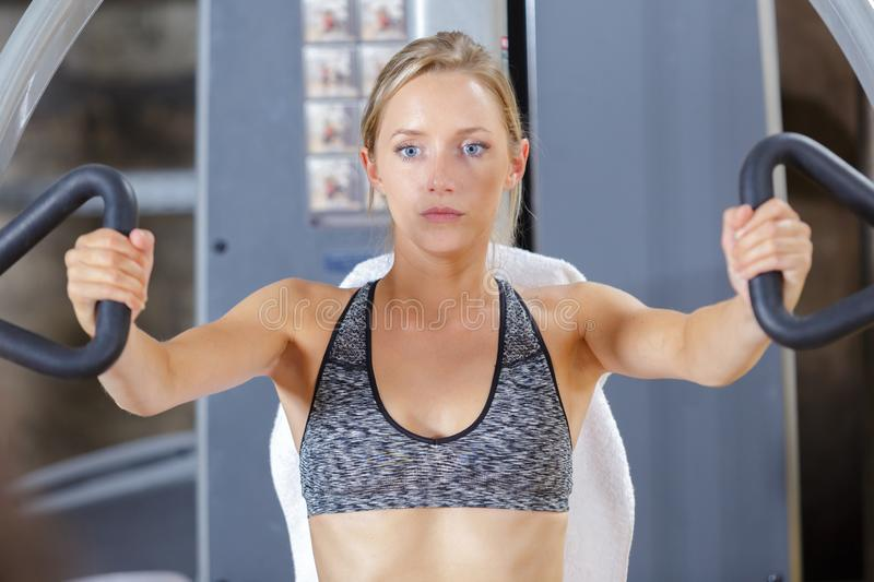 Girl doing upper body workout in gym. Woman royalty free stock images