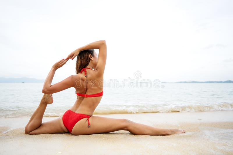 Girl doing yoga on the beach stock images