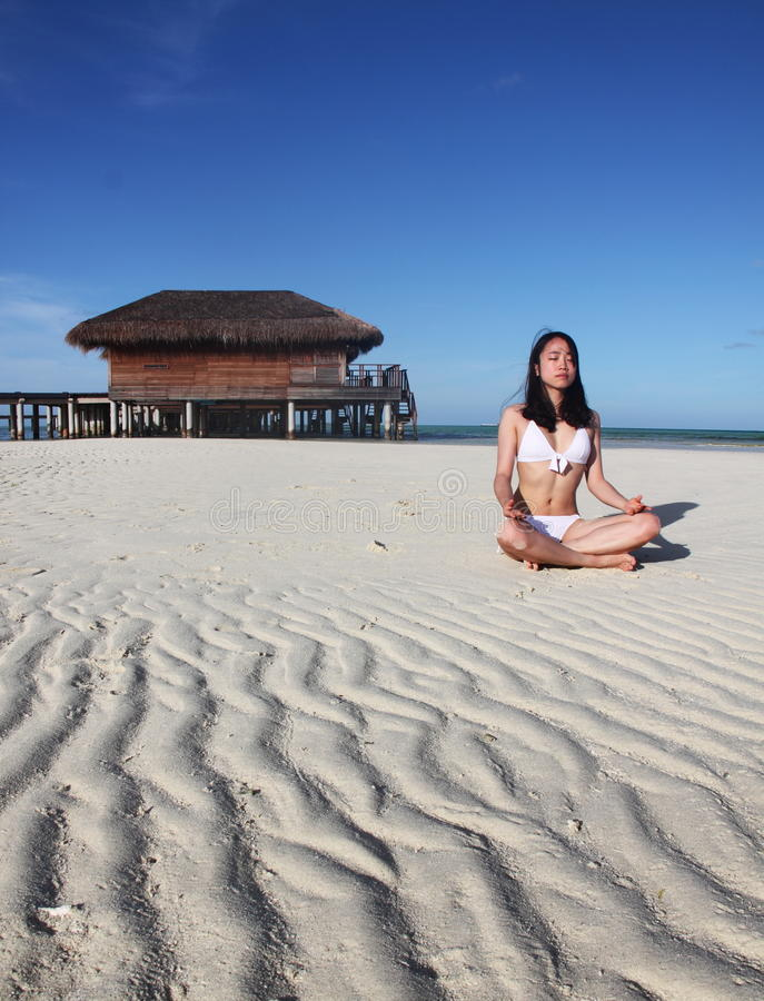 A girl doing yoga at beach royalty free stock photo
