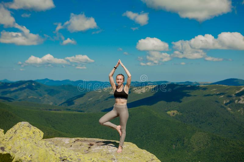 Girl doing yoga exercise lotus pose at the top of the mountain stock image