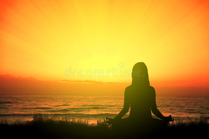 Girl doing yoga meditating in the beach sitting on the grass at sunset. Empty copy space stock photography