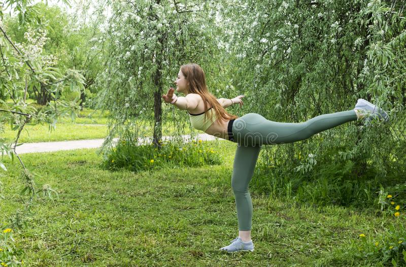 Girl doing yoga in nature, a young woman stands in a swallow pose royalty free stock photos