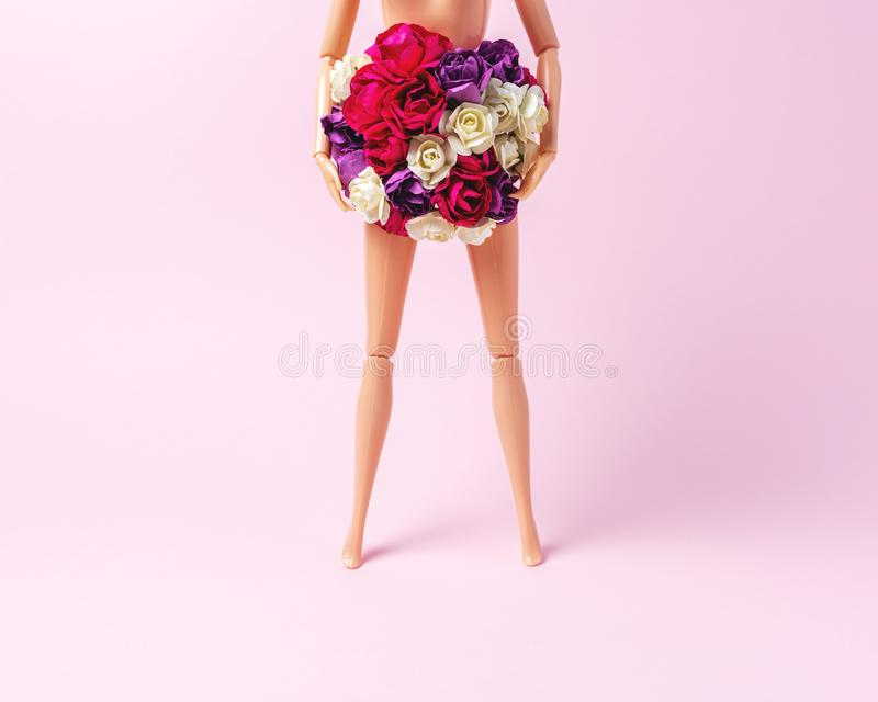 Girl doll with colorful flowers on pink background. Creative minimal fashion or love concept royalty free stock images