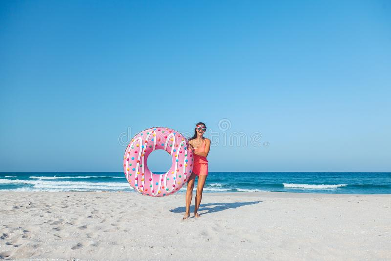 Girl with donut lilo on the beach stock photography