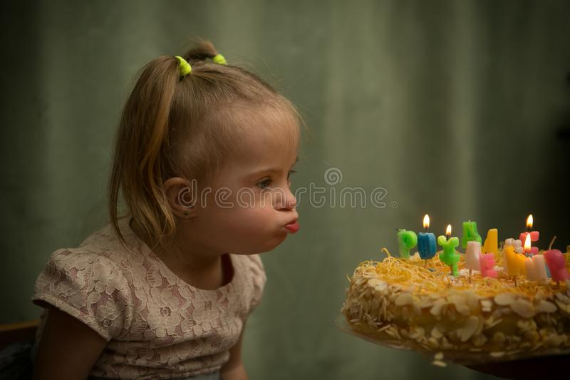 Girl with Down syndrome blows out the candles on her birthday cake stock photography
