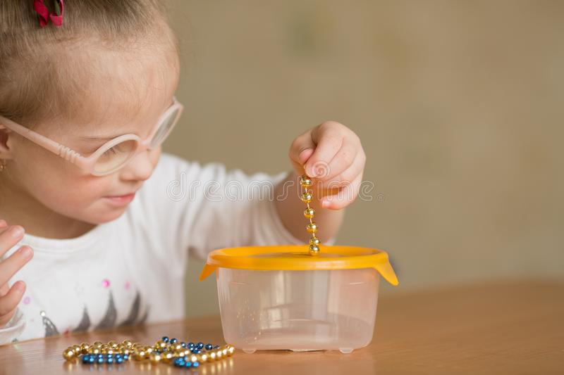 Girl with Down syndrome develops fine motor skills of hands stock photo