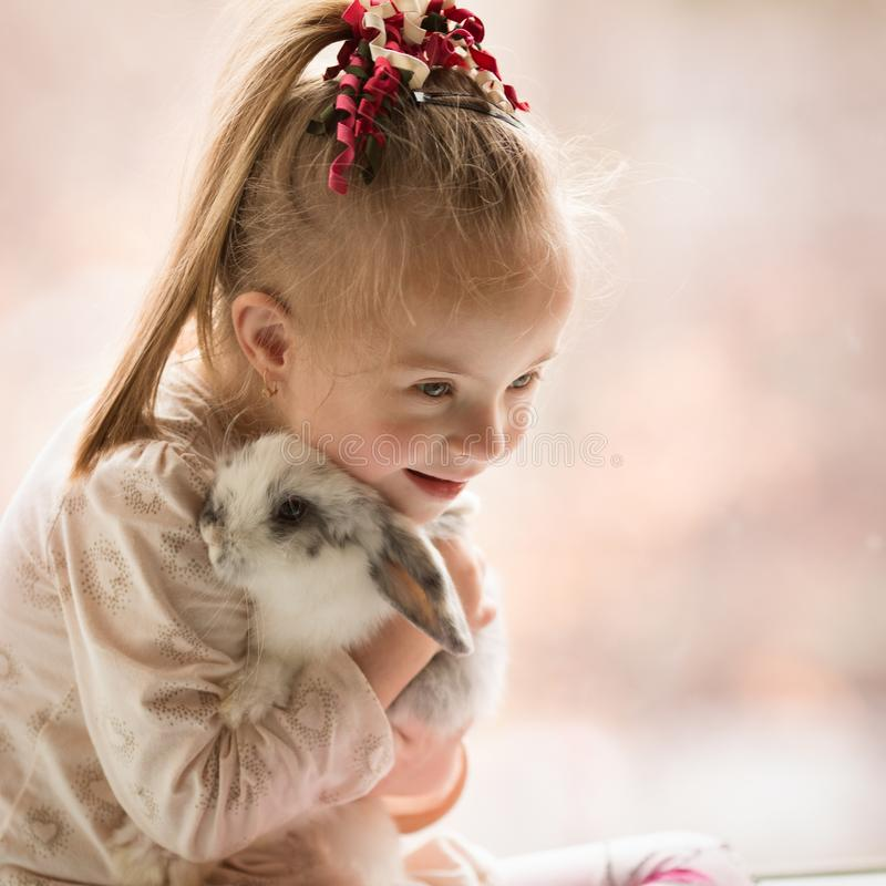 Girl with Down syndrome hugs rabbit stock photography