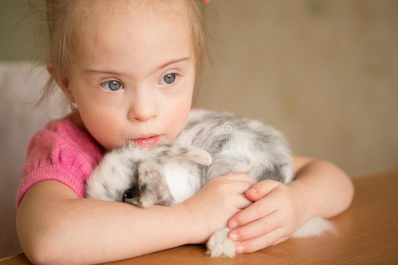 Girl with Down syndrome hugs the rabbit royalty free stock photos
