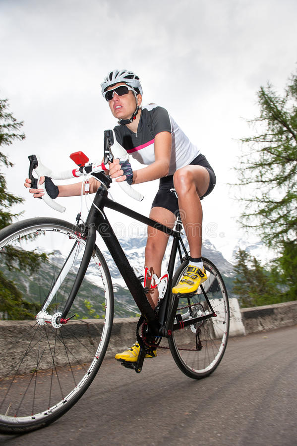 Girl downhill road cycling stock photography