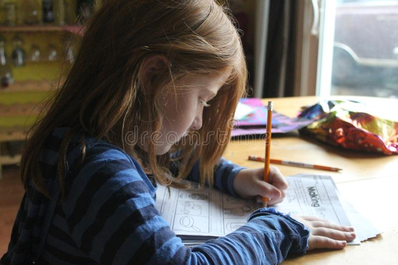 Girl Drawing On Brown Wooden Table royalty free stock photo