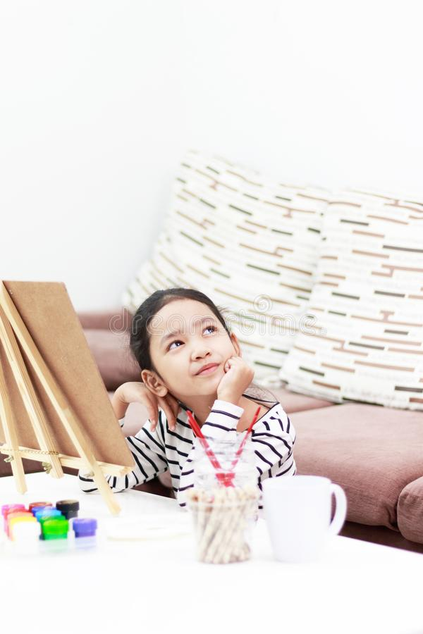 Girl drawing and dreaming at home stock images