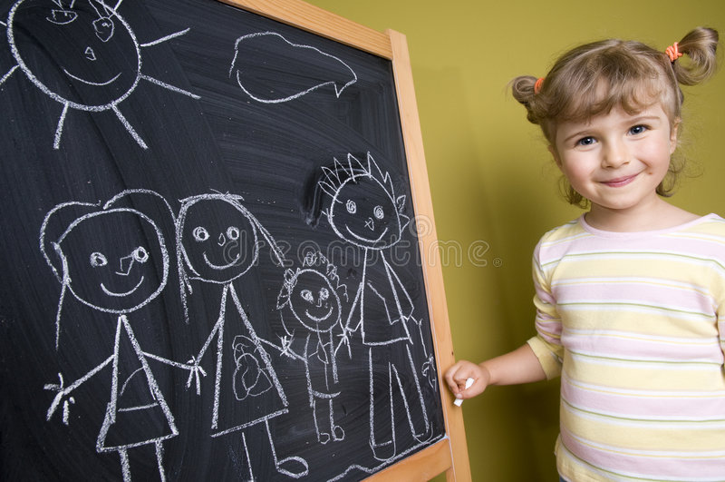 Girl drawing family on blackboard royalty free stock image