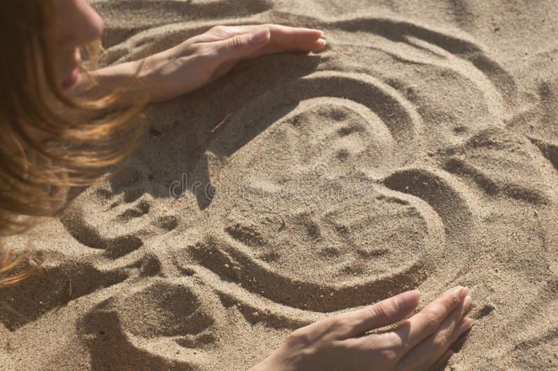 Girl drawing a heart on the sand at sunset in a summer love concept. Girl drawing a heart on the sand at sunset in a summer love concept stock photos