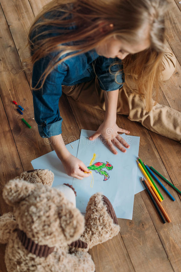 Girl drawing picture on floor at home, kids drawing concept royalty free stock image