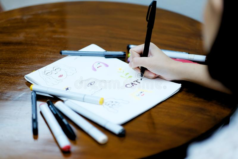 A girl drawing a picture on white paper by black pen stock images