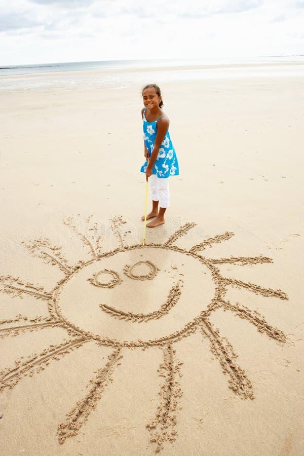 Girl drawing in sand. Smiling at camera royalty free stock photos