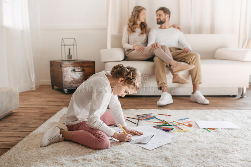 Girl drawing and sitting on floor, parents sitting on sofa behind royalty free stock photography
