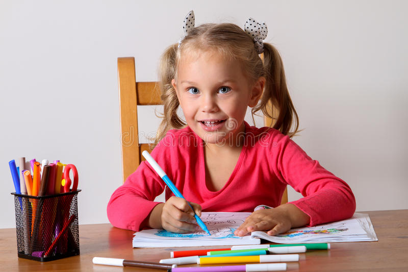 Girl drawing sitting at the table royalty free stock image
