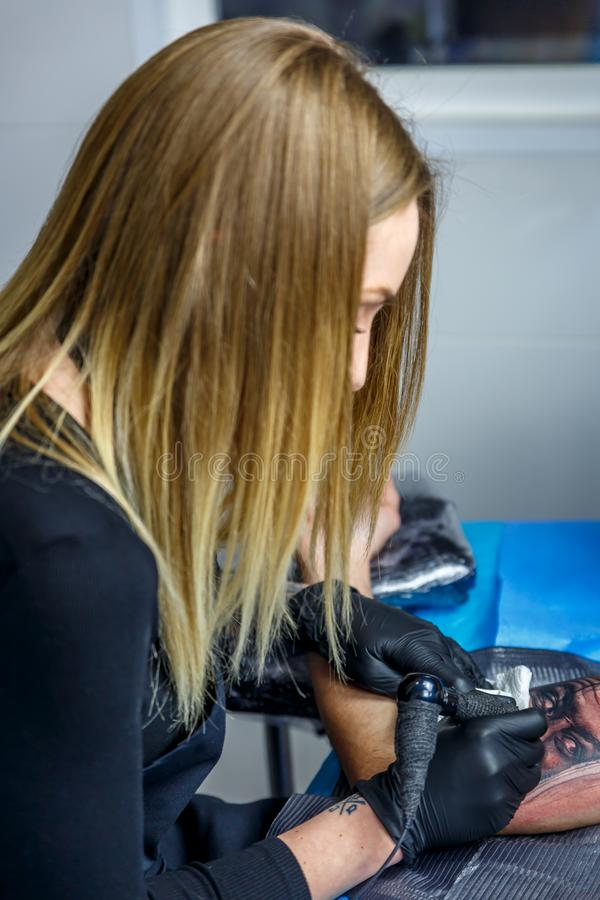 A girl is drawing a special tattoo on the arm of a boy in her narrow studio. A girl is drawing a special tattoo on the arm of a boy in her little and narrow royalty free stock photos