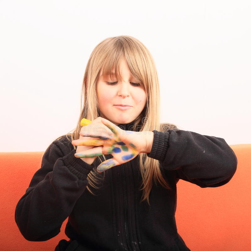 Girl drawings on hand. Drawing kid sitting on orange couch - smiling concentrated blond girl with drawed colorful face on palm and fingers of her hand stock photography
