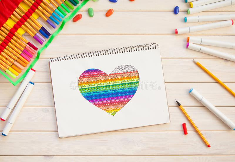 Girl draws markers postcard with a color heart. Many bright mark royalty free stock photo