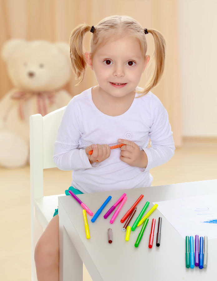 The girl draws with markers. Pretty little blonde girl drawing with markers at the table.Girl holding in hands blue marker.The concept of preschool development royalty free stock photos