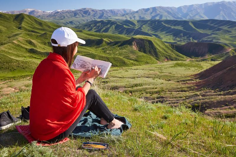 Girl draws on nature spring landscape. Painting outdoors. Kazakhstan. Mountain landscape royalty free stock photos