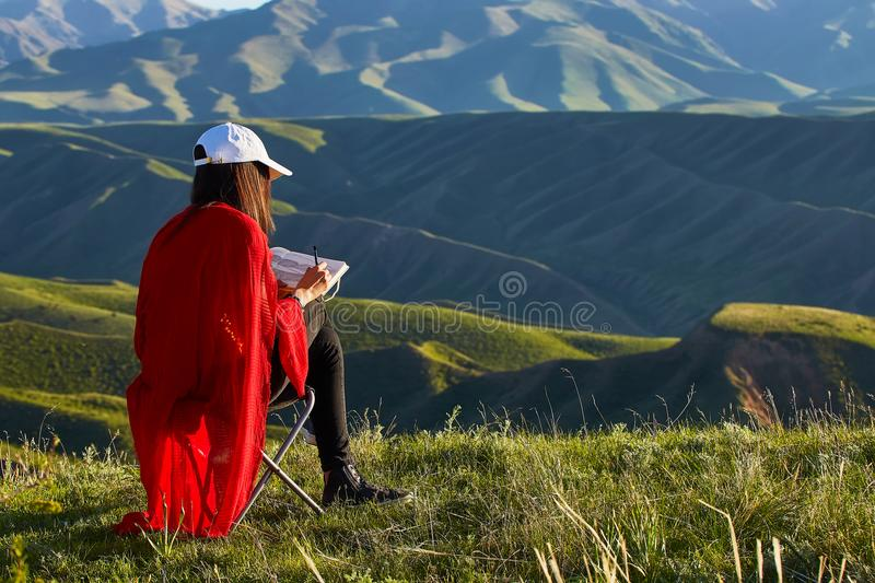 Girl draws on nature spring landscape. Painting outdoors. Kazakhstan. Mountain landscape royalty free stock images