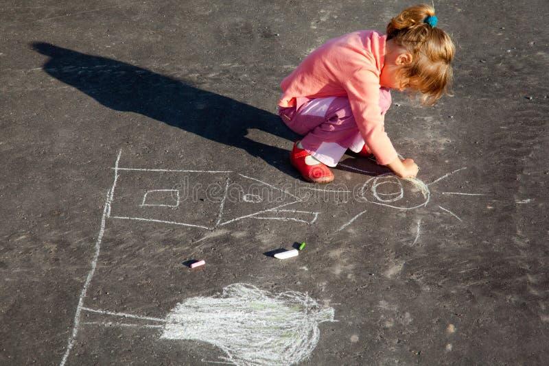 Girl draws painting line a chalk on asphalt royalty free stock photos
