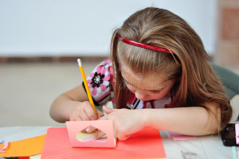 The girl draws with a pencil, signs a paper card, eco-friendly material royalty free stock image