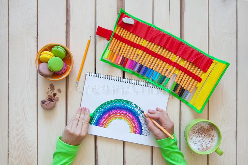 Girl draws a rainbow. Positive drawing. Art therapy and relaxation. royalty free stock photos